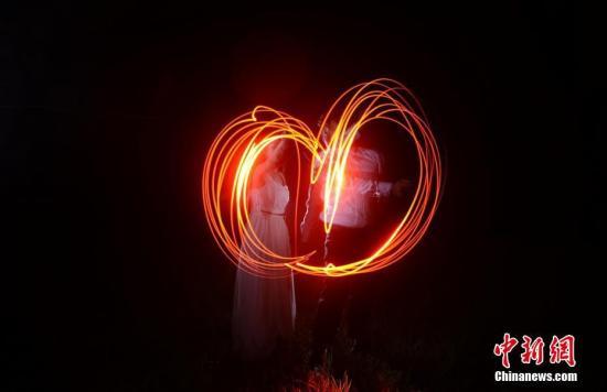 资料图:情侣用手电筒画出了心形的图案。杨华峰 摄