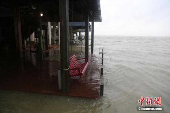 """大西洋飓风""""哈维""""于8月25日夜间登陆得州南部沿海地区后,26日上午,风速已降至1级。图为休斯敦东南方向60公里的kiki岛沿海居民楼。26日上午,海水恢复平静无大浪,海平面上涨正浸入居民楼平台。<a target='_blank' href='http://www.chinanews.com/'>中新社</a>记者 曾静宁 摄"""