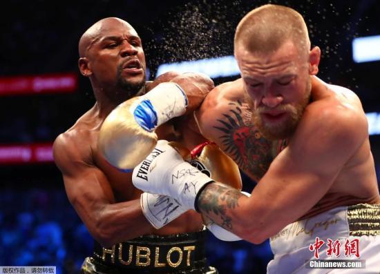 """资料图:拳击巨星梅威瑟与UFC传奇,""""嘴炮""""麦格雷戈一战在赌城拉斯维加斯上演,在比赛中,梅威瑟凭借出色的防守最终笑到了最后,拿下了WBC特制的""""金钱金腰带""""。在比赛中,梅威瑟初始阶段一直在防守,最后时刻突然爆发,连续攻击对手,""""嘴炮""""被TKO。图为梅威瑟击中麦格雷戈瞬间。"""