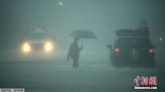 资料图:民众在大雨中涉水前行。