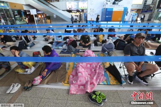 当地时间2017年8月29日,韩国首尔,首尔火车站买票窗口前,韩国民众排队购买中秋节期间的火车票。