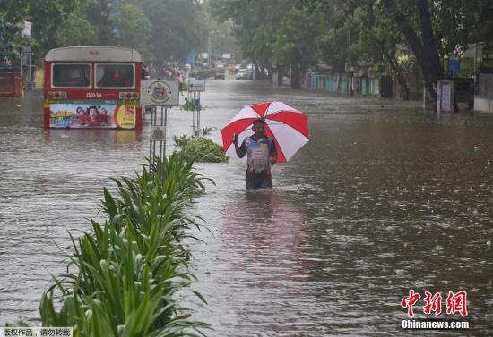 资料图:印度遭洪水侵袭,孟买民众在积水中前行。