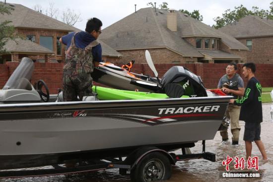 """大西洋飓风""""哈维""""给休斯敦城造成严重内涝。当地时间8月29日,更多休斯敦华人利用私人船只、皮卡结成临时救助小队帮助被困华人及当地民众撤离。图为休斯敦华人志愿者卸船作救灾准备。 记者 曾静宁 摄"""