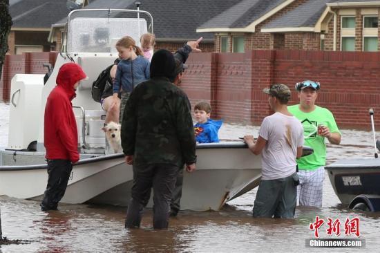 """大西洋飓风""""哈维""""给休斯敦城造成严重内涝。当地时间8月29日,更多休斯敦华人利用私人船只、皮卡结成临时救助小队帮助被困华人及当地民众撤离。图为休斯敦华人志愿者协助当地民众撤离。 <a target='_blank' href='http://www.chinanews.com/'>中新社</a>记者 曾静宁 摄"""