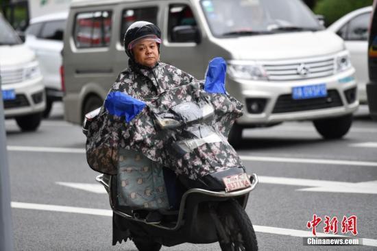 资料图:8月30日,成都市民增添衣物出行。。 中新社记者 张浪 摄