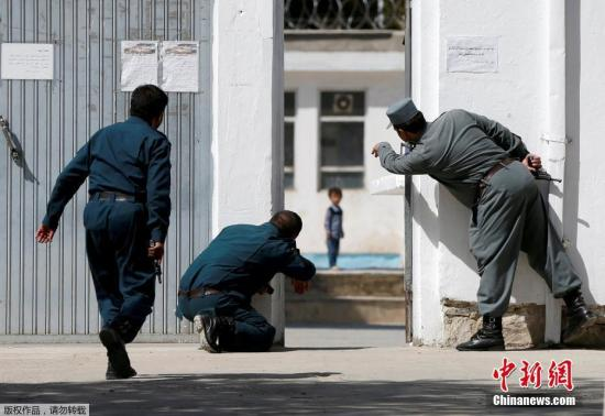 """2017年8月29日讯,阿富汗喀布尔,25日发生清真寺的遇袭事件,目前已造成超过30人死亡,至少80人受伤。据悉,此次袭击至少有4名武装分子参与,其中2名武装分子在清真寺中实施了自杀式爆炸袭击,另有2名武装分子被警方击毙。由于事发时有大批民众在清真寺祷告,导致此次袭击伤亡惨重。事件发生后,极端组织""""伊斯兰国""""表示对该事件负责。28日,英国《每日邮报》刊登出一组袭击事件的现场照片,一名叫阿里・阿默德的4岁小男孩遭遇颇让人揪心。图为袭击事件发生后,阿富汗警察正让阿默德逃离现场,当时武装分子还在和阿富汗军警进行交火,现场十分混乱。"""