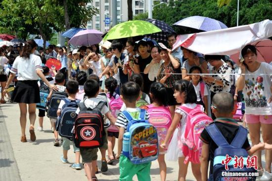 资料图:8月31日,福州市仓山区第五中心小学,许多一年级新生家长们来到校门口等候放学的孩子。张斌 摄