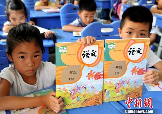 资料图:福州市仓山区第五中心小学一年级新生展示刚领取的语文统编教材。(张斌 摄)