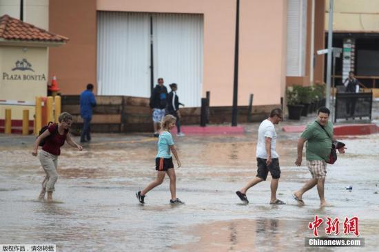 """当地时间2017年8月31日,墨西哥洛斯卡波斯,当地遭受热带风暴""""莉迪亚""""袭击,海面掀起巨浪。图为几位游客在漫水街道穿行。"""
