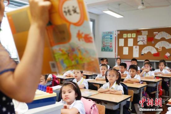一年级新生正在认真听讲《语文》教材的内容。 殷立勤 摄