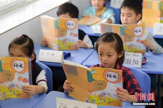 资料图:合肥市南门小学的一年级新生在阅读新编语文教材。中新社记者 张娅子 摄