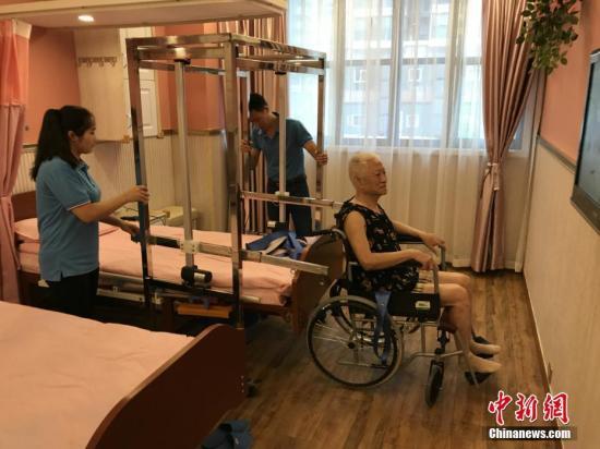 """资料图:重庆一养老服务所自主设计的一款专为失能老人服务的""""移动机""""正式投用。钟欣 摄"""
