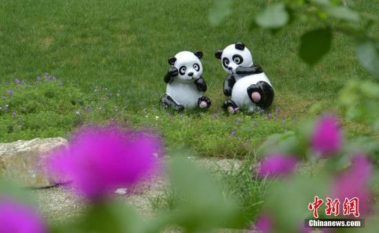 资料图:成都三环路边草丛中的熊猫雕塑。 中新社记者 刘忠俊 摄