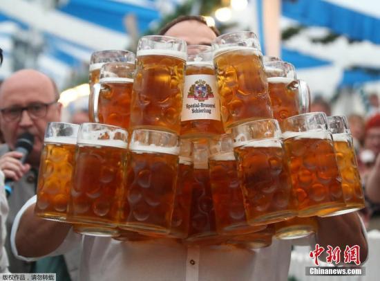 资料图:一名男子手捧多杯啤酒。