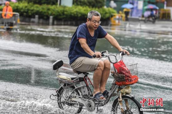 """9月4日,广州江燕路上,广州市民骑车经过积水路段。当日,受台风""""玛娃""""影响,广东东部和中部沿海地区遭遇暴雨。其中,广州多区发布暴雨红色预警,中小学校、幼儿园、托儿所停课。 <a target='_blank' href='http://www.chinanews.com/'>中新社</a>记者 陈骥�F 摄"""