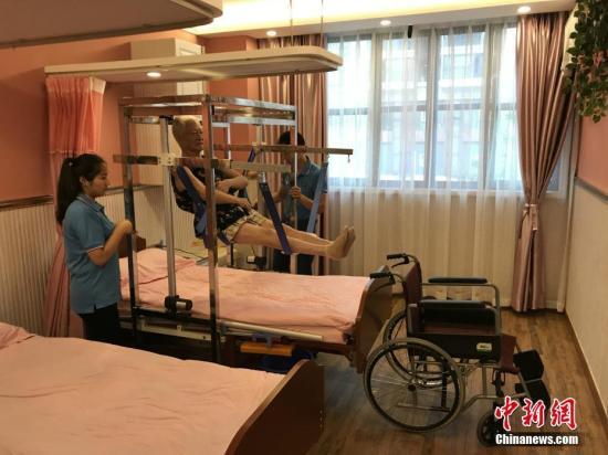"""资料图:重庆一养老服务所自主设计的一款专为失能老人服务的""""移动机""""正式投用。只要开启设备,就能完成老人托举、移动等工作,减少了因护理不当给老人造成的二次伤害,减轻了老人的痛苦及护理人员的劳动强度。钟欣 摄"""