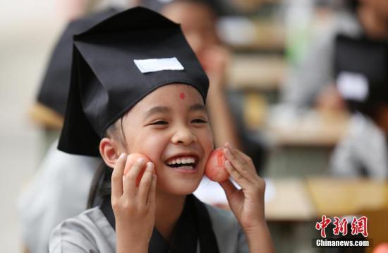 """9月4日,广西柳州市融安县第二实验小学举行的一年级新生入学""""开笔礼""""仪式上,一名学生展示老师发的""""红鸡蛋""""。当日,是广西柳州市中小学2017秋季开学第一天。该校举行一年级新生""""开笔礼""""仪式,学生和老师身穿传统汉服,进行""""正衣冠""""""""击鼓明智""""""""诵读经典""""""""感恩师长""""""""启蒙开笔""""""""送红鸡蛋""""等环节。以此教育和引导新学生学习中华传统文化,传承文化经典。 谭凯兴 摄"""