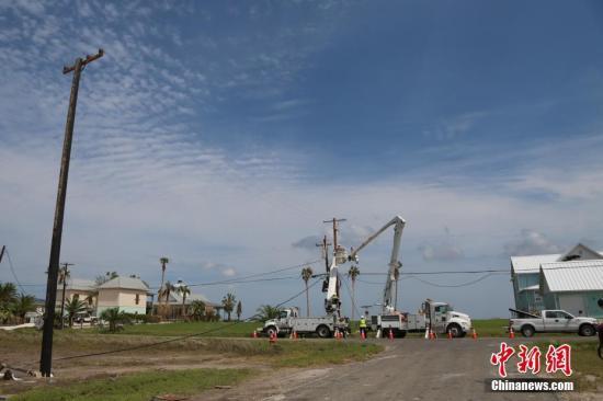"""当地时间9月3日,""""哈维""""袭击后的第十天,飓风登陆地得州南部沿海小镇石港(Rockport)已进入灾后重建阶段。图为当地市镇人员在抢修供电设施,目前当地仍处于断电状态。记者 曾静宁 摄"""