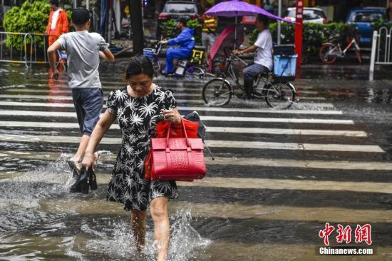 """资料图:市民提鞋走过积水路段。当日,受台风""""玛娃""""影响,广东东部和中部沿海地区遭遇暴雨。<a target='_blank' href='http://www.chinanews.com/' _fcksavedurl='http://www.chinanews.com/'></table>中新社</a>记者 陈骥旻 摄"""
