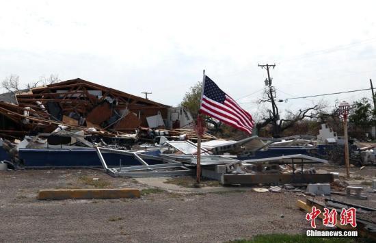 """资料图:当地时间2017年9月3日,""""哈维""""袭击后的第十天,飓风登陆地得州南部沿海小镇石港(Rockport)已进入灾后重建阶段。图为受损房屋边插上了崭新的美国国旗。中新社记者 曾静宁 摄"""