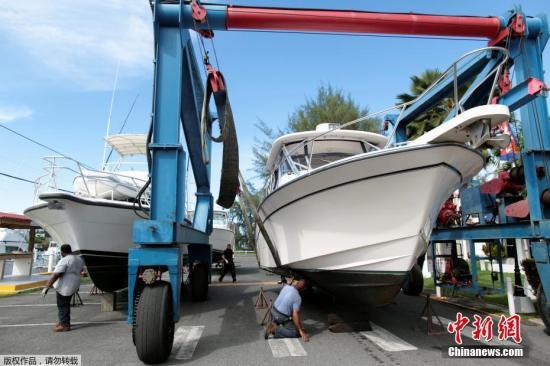 """当地时间2017年9月4日,波多黎各圣胡安,工人将船安放至干船坞,准备迎接刚升级为4级风暴的""""艾玛""""飓风。"""