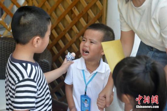 资料图:大班小朋友安慰哭泣的新生。吕明 摄