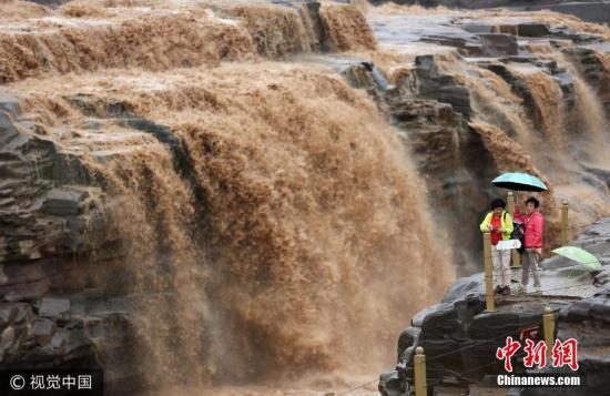 9月5日,游客在黄河壶口瀑布景区游览观赏瀑布。受近日黄河中游部分地区连续出现强降雨影响,位于山西吉县和陕西宜川县之间的黄河壶口瀑布迎来秋汛,主副瀑布形成壮美瀑布群,吸引了众多游客前来观赏。王新 摄 图片来源:视觉中国