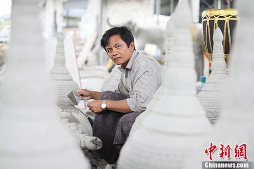"""7月2日,来自缅甸彬马那的雕刻师吴吉(音译)在进行雕刻工作。""""朋友说,来中国工作收入更高点。""""经朋友介绍,吴吉带着手艺来到中国瑞丽务工。今年60岁他将全家都搬到了与中国瑞丽接壤的缅甸木姐居住,周末吴吉可以从瑞丽回到木姐与家人团聚。月收入2100元人民币已能让吴吉供养一个家庭。""""我要努力工作,为孩子们创造一个更好的未来。""""吴吉说道。 中新社发 杨立 摄"""