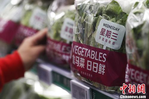 """9月6日,在上海一家""""网红""""电商体验店内,顾客正在挑选标注""""星期三(当日)""""送达门店的新鲜蔬菜。 <a target='_blank' href='http://www.chinanews.com/'>中新社</a>记者 张亨伟 摄"""