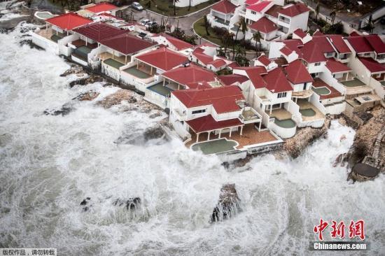 """当地时间9月6日,飓风""""艾尔玛""""过境圣马丁岛后,岛上一片狼藉。海边的几栋房屋如""""孤岛""""般被大浪包围。"""
