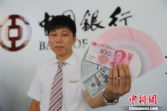 山西太原,银行工作人员正在展示人民币、美元。 张云 摄