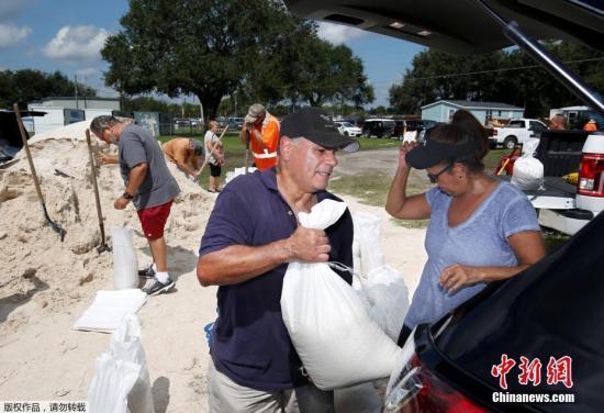 在美国佛州,居民排几小时的长队取沙袋,为飓风登陆做准备。