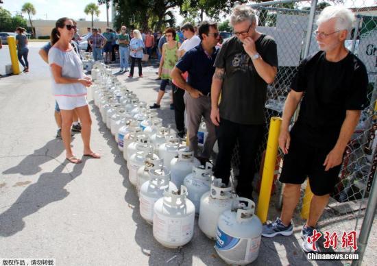 """随着飓风""""艾尔玛""""不断逼近,美国佛罗里达州民众除了囤水囤粮,也都纷纷前往加油站给汽车加油。但由于需求量太大,一些加油站的汽油已经告罄。"""