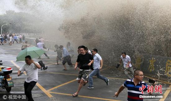"""资料图:市民和游客在钱塘江杭州段观看""""鬼王潮""""。吴煌 摄 图片来源:视觉中国"""