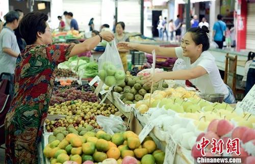 资料图:图为农贸市场内民众正在购买水果。记者 刘忠俊 摄