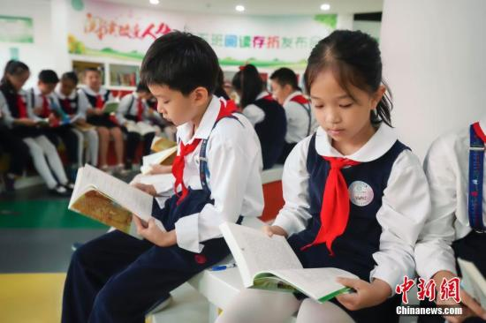 资料图:小学生们在读书。中新社记者 贾天勇 摄