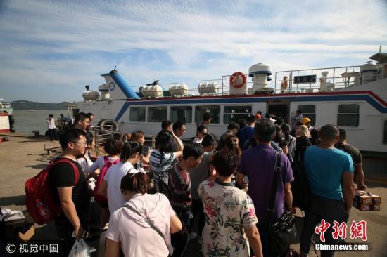 """9月12日下午,舟山市嵊泗李柱山码头,游客们正在有序地登轮离港。受今年第18号台风""""泰利""""影响,舟山岛际交通部分航线已经停航。姚峰 摄 图片来源:视觉中国"""