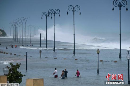 """当地世界9月11日,古巴民众走在被洪水淹没的哈瓦那街头。据外媒报道,古巴的民防组织称,飓风""""艾尔玛""""已经导致该国至少10人死亡。当地时间8日晚,飓风""""艾尔玛""""在中部卡马圭省北部岛屿登陆,古巴东部和中部有100多万居民被疏散。"""