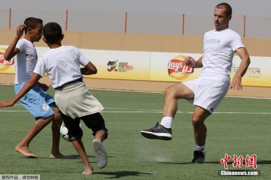 欧足联主席亚历山大·切费林(右)与难民小孩们在球场上玩耍。