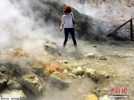 索尔法塔拉火山是一座休眠火山,如今仍在喷发出硫磺蒸汽。图为一名女子近距离的观察索尔法塔拉火山的一个蒸汽喷发出口。(资料图)