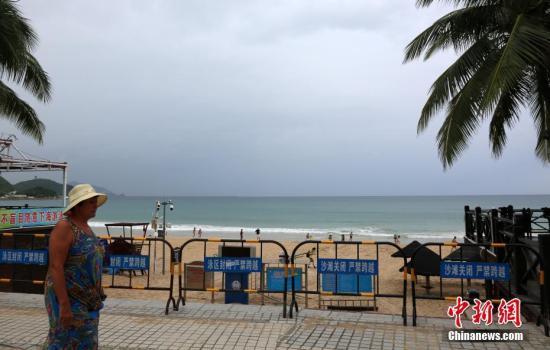 """9月14日,海南三亚大东海景区,游客从已经封闭的海滩入口处经过。受今年第19号台风""""杜苏芮""""的影响,三亚海滩关闭,暂停涉海旅游。 记者 尹海明 摄"""