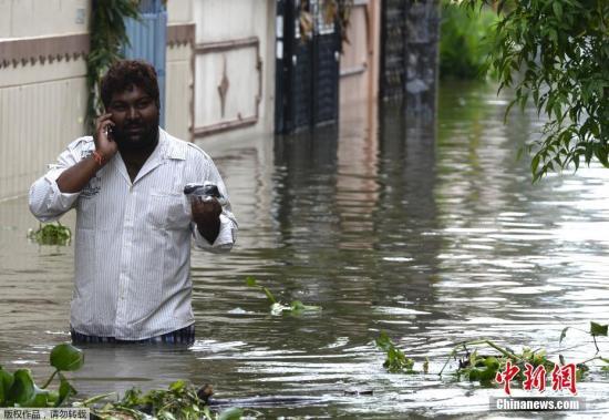 当地时间9月14日,印度暴雨致海得拉巴发生洪涝,低洼地段街道房屋被淹。图为当地居民在被淹没的街道上行走。