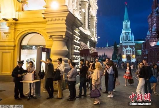 塔斯社援引俄安全部门消息说,莫斯科安全部门当天接到超过20个匿名电话,称莫斯科市内的火车站、购物中心、学校、电影院等人员密集场所可能藏有炸弹。图为莫斯科红场,等待进入古姆国立百货商店的顾客排队接受安全检查。