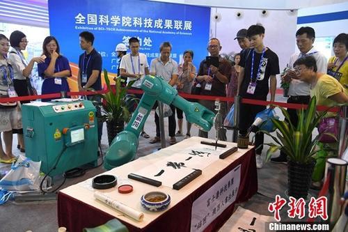 9月14日,在广西南宁举办的第14届中国-东盟博览会上,一台机器人正在进行书法展示,吸引众多观众围观。中新社记者 俞靖 摄