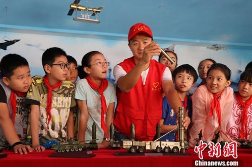 资料图:志愿者在给小学生讲解各军事装备模型。中新社记者 张娅子 摄