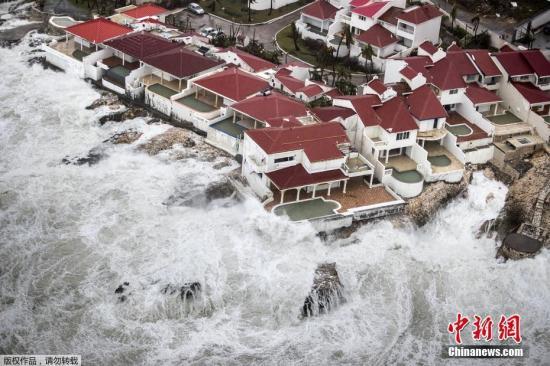"""资料图:飓风""""艾尔玛""""经过时,航拍加勒比海边的几栋房屋如""""孤岛""""般被大浪包围。"""