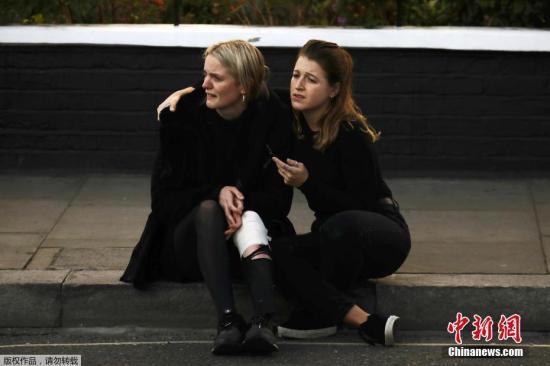 伦敦紧急救援部门已经抵达现场展开救援。图为受伤民众坐在台阶上。