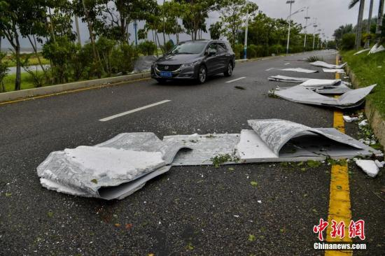 三亚海棠湾一工地铁皮广告护栏被大风吹到,铁皮泡沫散落在道路上。骆云飞 摄