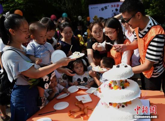 """9月16日,重庆杨家坪动物园为大熊猫""""新星""""举办了35岁生日会,吸引众多民众参与。活动现场,不仅有工作人员为""""新星""""送上特别制作的生日蛋糕,还有小朋友亲手绘制十米长卷送上生日祝福。同时,工作人员还向前来参加生日会的民众分发生日蛋糕,共同庆祝大熊猫""""新星""""35岁生日。 周毅 摄"""