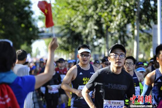 热心市民手举国旗为跑者们加油呐喊。中新网记者 李霈韵 摄